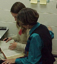 Two women looking at a book together