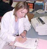 Physician filling out paperwork at a desk