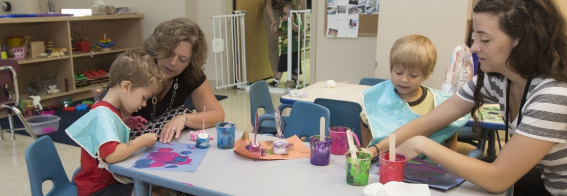 Clinical educators helping children with paint projects