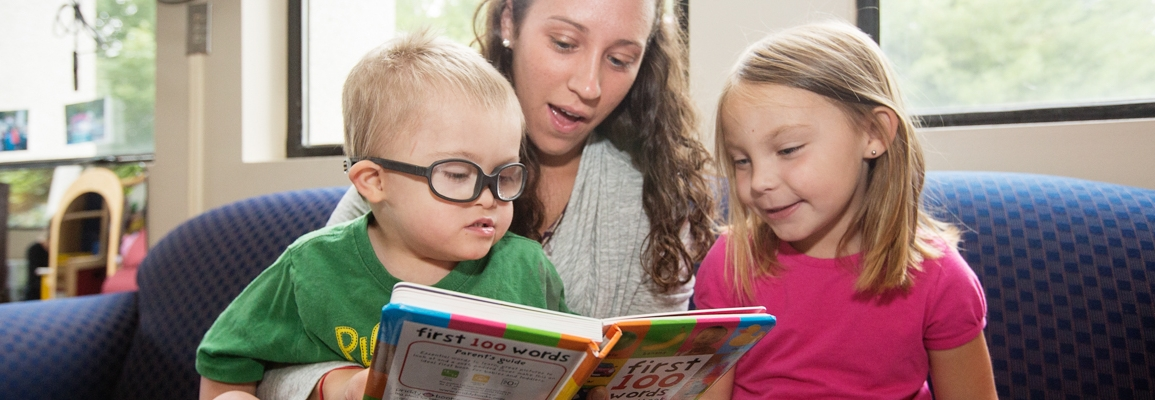 Clinical educator helping two children read a book