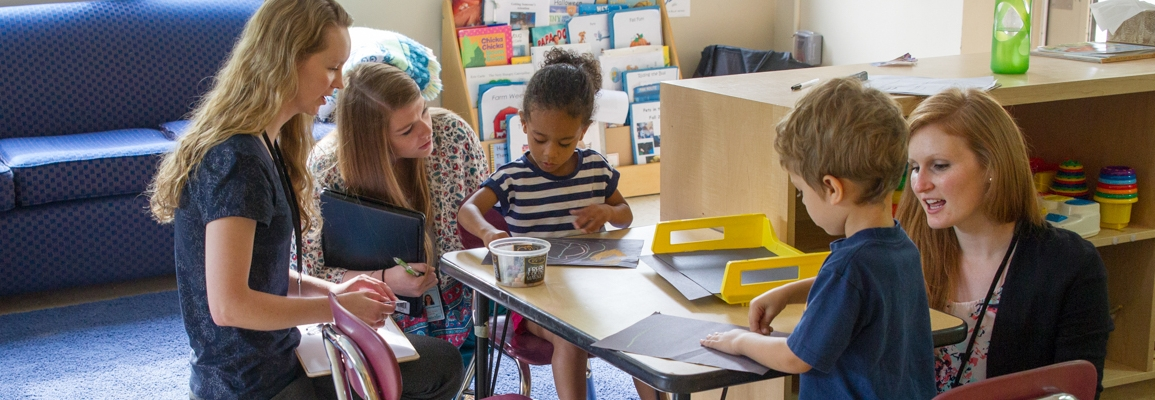 Children and clinical educators sitting around a table