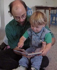 Man reading a book with a child sitting on his lap