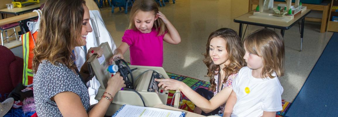 Clinical educator explaining testing equipment to children